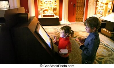 boy and girl looks at interactive display in museum