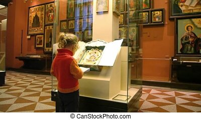 little girl drawing copy of exhibit in museum