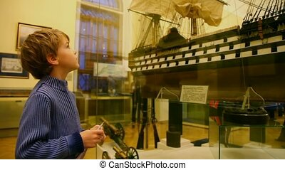 boy take a good look on model of boat in museum