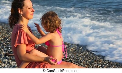 young mother with her little daughter embracing in pebble beach near sea