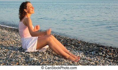 young happy woman has fun sitting ob pebble beach, sea in...