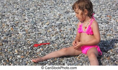 little girl dressed in swimsuit sitting on pebble beach fingering stones