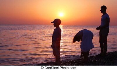 family throwing pebbles to water, sunset sea in background