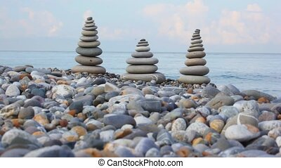 stone stack on pebble beach, sea and clouds in background