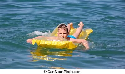 young boy oaring on yellow inflatable mattress in sea