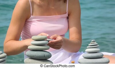 unidentified woman building stone stack on pebble beach, sea in background