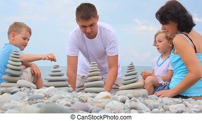 family building stone stacks on pebble beach, sky in background
