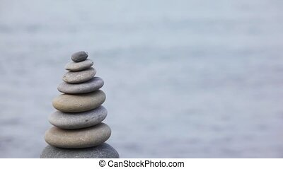 stone stack on pebble beach, sea in background, vertical panning
