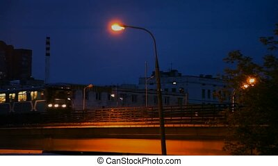 light rail train going in residential area of night city,...