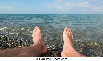 male foots of adult man lying on pebble beach, view on sea