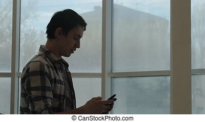 Happy man stands near window and chats on cell phone....