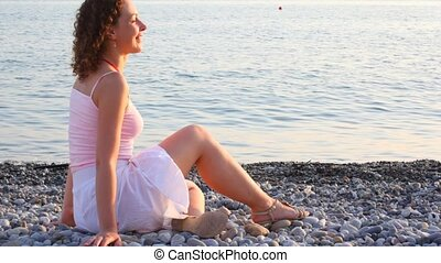 young smiling woman sitting on pebble beach, sea in background