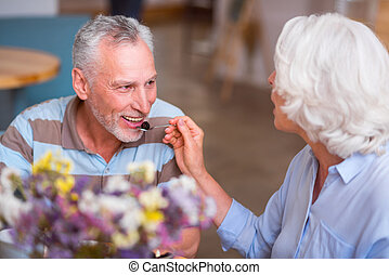 Positive senior couple having a meal - Try it. Cheerful...