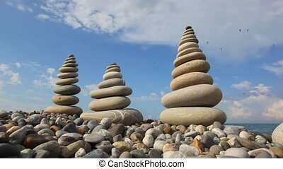 pebble stack on the stone seashore, sea and sky with birds in background