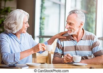 Joyful senior couple sitting at the table - Warm atmosphere....