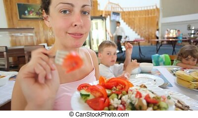 smiling woman bringing red tomato on fork to camera in cafe