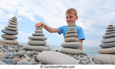 boy building stone stack on pebble beach, sea in background