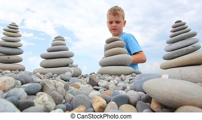 boy building stone stack on pebbles, sky in background