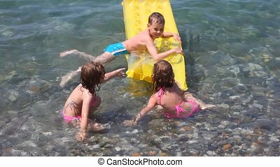 happy smiling kids playing with inflatable mattress in water...
