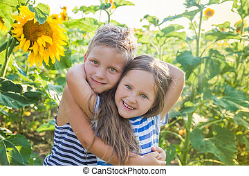 Boy and girl hugging among sunflower field - Happy boy and...
