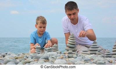 father with son building stone stacks on pebble beach, sea in background
