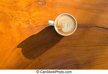 Close up cup of latte coffee on wooden table with shade of...