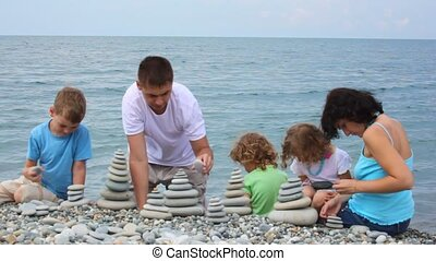 family building stone stacks on pebble beach, sea in background