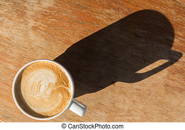 Cup of latte coffee on wooden table with shade of sun light...