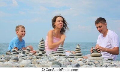 family building pebble stacks on pebble beach, sea in...