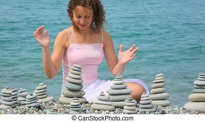 young woman building stone stack on pebble beach, sea in background