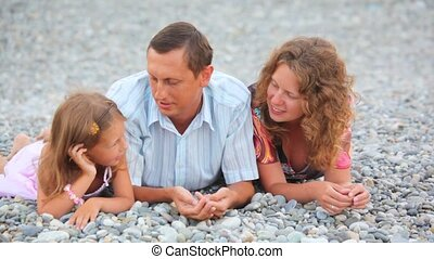 happy family of three persons lying on pebble beach and talking