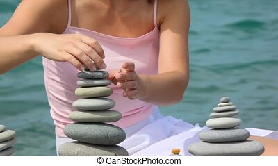 headless woman building stone stack on pebble beach, sea in...