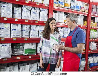 Smiling Salesman Assisting Customer In Buying Pet Food -...