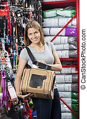 Smiling Woman Showing Pet Carrier In Store - Portrait of...