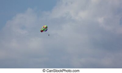 parasailing, man with colour parachute flying in sky with...