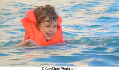 little girl dressed in orange inflatable waistcoat swimming...