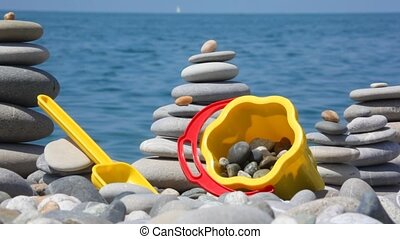 stone stacks and children\'s bucket with scoop on pebble seacoast