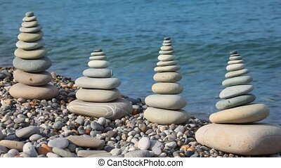 pebble stack on the stone seacoast, sea in background
