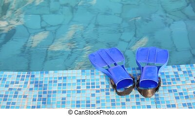 blue flippers is on mosaic edge of swimming pool with clear...