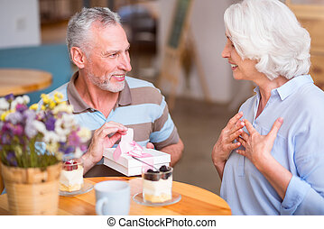 Pleasant senior man giving present to his wife - Want to...