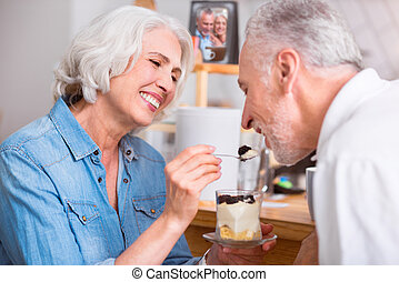 Cheerful senior couple resting in the cafe - One spoon for...