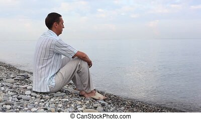 man sitting on pebble coast and looks at sea, side back view