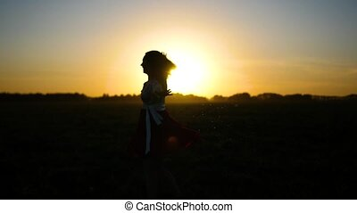 girl in a dress spinning in the sunset