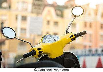 Steering wheel of yellow scooter.