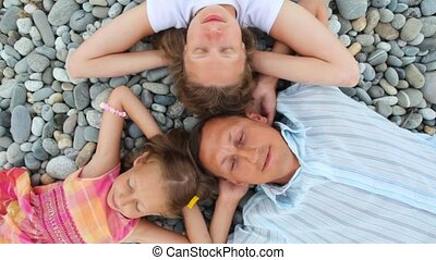 happy family of three persons lying on pebble beach, top view