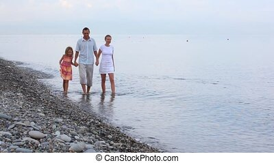 family of three persons walking in sea surf, join hands, to...