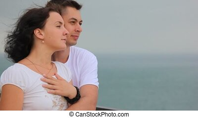 standing in beach young couple looks at sea, hairs swaying...