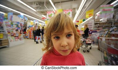 little girl sitting in shopping trolley in supermarket