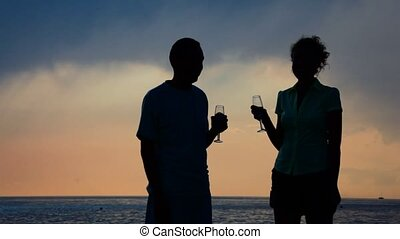 silhouettes of man and woman with goblets drinking champagne and kissing