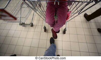 buyer with camera and shopping trolley going in mall, view on floor